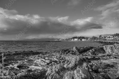 A Black & White image of Largs Looking over Lichen Covered Rocks to the Town in Canvas Print