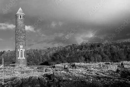 Black & White Image of Largs Lichen Covered Rocky Foreshore and the Pencil Monument Commemorating the Viking Battle of Largs in 1263 Wallpaper Mural