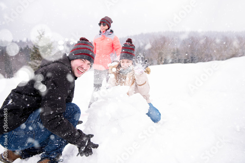 Fototapeta group of young people making a snowman obraz