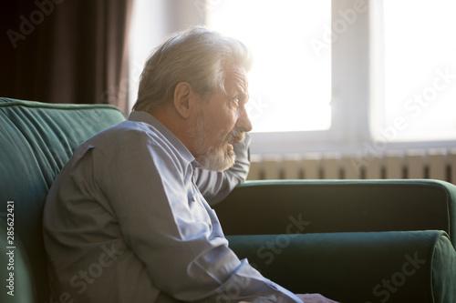 Fototapeta  Thoughtful senior grandpa sit alone on sofa thinking of loneliness
