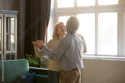 Cheerful retired spouses laughing dancing in living room - 285624227