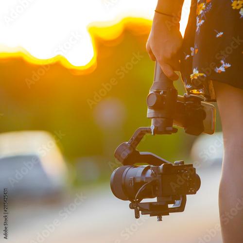 Obraz na plátne  A girl holding a camera mounted on a gimbal.