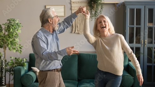 Joyful active old retired romantic couple dancing in living room Wallpaper Mural