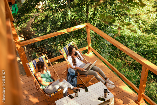 Fotografia Two female friends relaxing on a wooden balcony in woods.