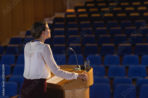 Photo Businesswoman practicing for speech in the empty auditorium