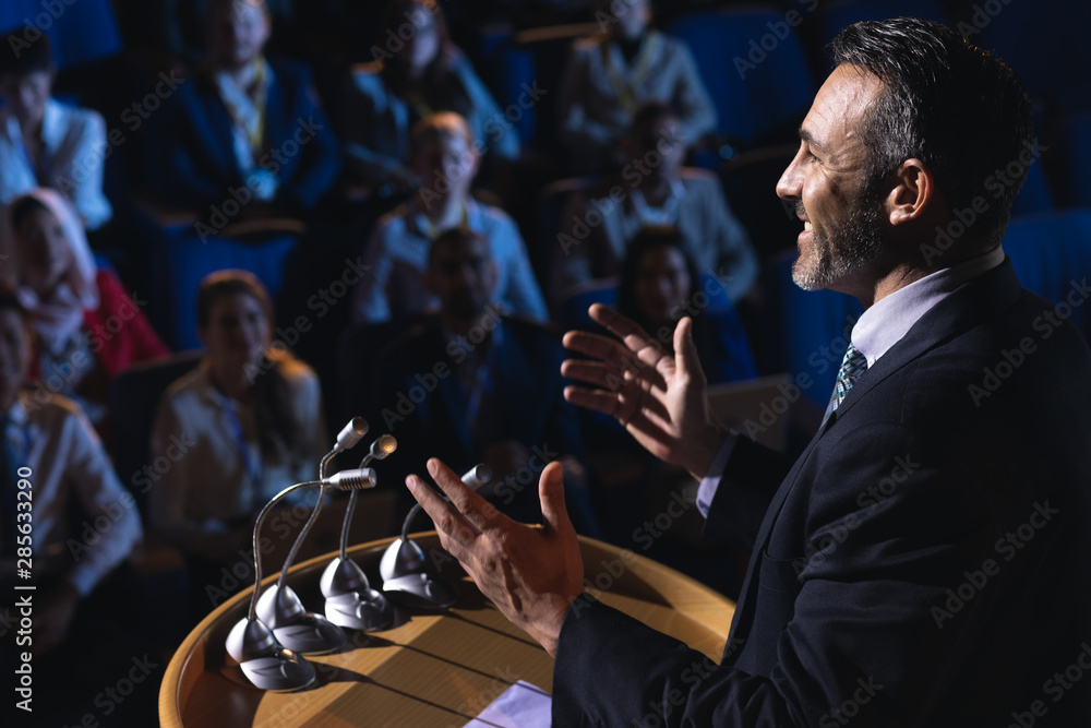 Fototapeta Businessman standing and giving presentation in the auditorium