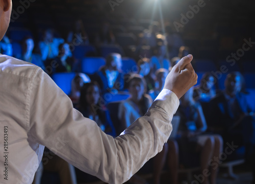 Businessman giving presentation in front of audience in auditorium Canvas Print