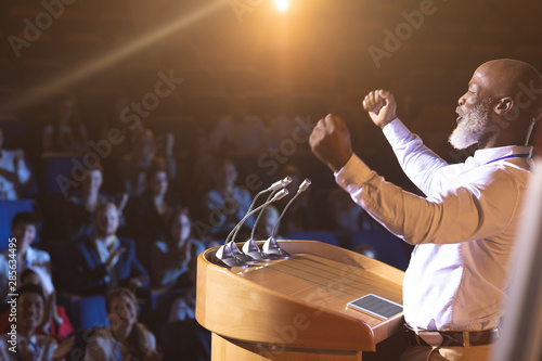 Fotografia Businessman standing near podium and giving speech to the audience in the audito
