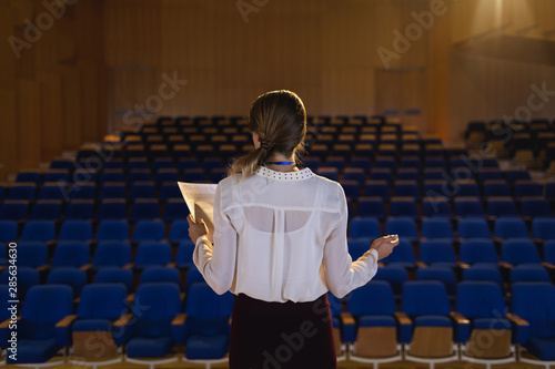 Photo Businesswoman practicing and learning script while standing in the auditorium