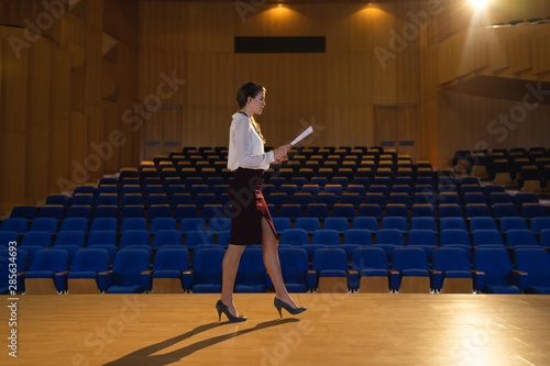 Photo Businesswoman practicing and learning script while walking in the auditorium