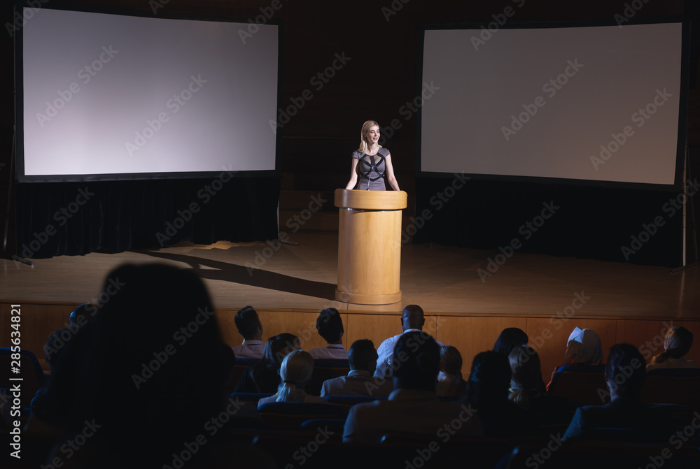 Fototapeta Businesswoman standing around podium and giving presentation to the audience