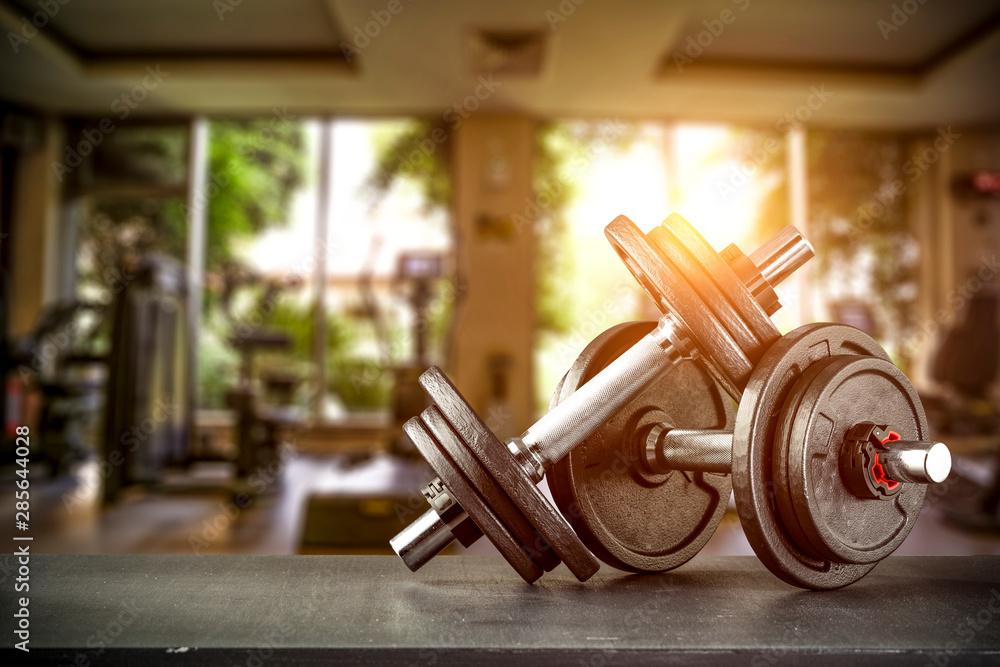 Fototapeta Dumbbells on desk and gym interior