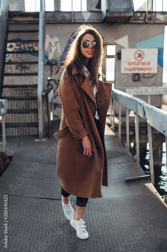 Beautiful Young Stylish Girl in Coat Walking in the Spring Beach at Sunset Wall mural