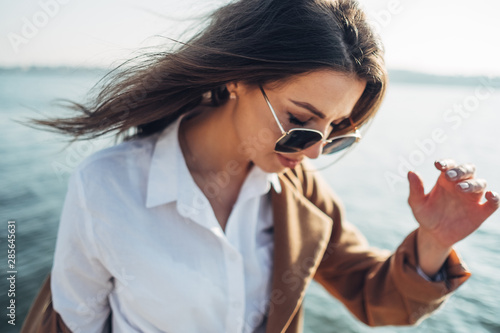 Beautiful Young Stylish Girl in Coat Walking in the Spring Beach at Sunset
