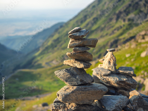 Valokuvatapetti Stone stack with balanced stones on blurred mountain background in sunset warm l