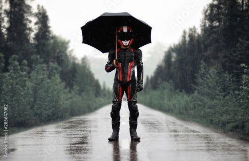 Valokuva Motorcyclist in full gear and helmet with umbrella in the rain