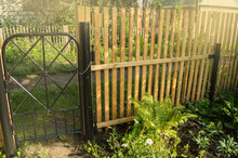 Rustic New Wooden Fence With Black Metal Posts And Gates, Garden And Vegetable Garden Fence On A Sunny Summer Day, Against The Background Of Plants And Trees