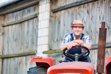 Smiling Mature Male Farmer Sitting On Tractor