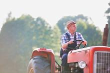 Mature Farmer Driving Tractor ...