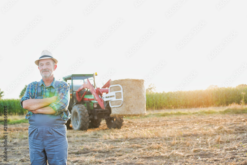 Fototapety, obrazy: Confident senior farmer standing against tractor in field with yellow lens flare in background