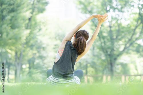 Obraz 公園でヨガ・ストレッチをする女性 - fototapety do salonu
