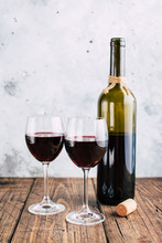 Two Glasses Of Red Wine And A Bottle, Gray Stucco Background