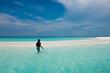 Man plants an anchor on a beach in the Maldives