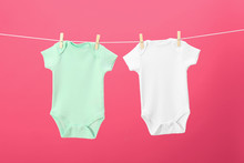 Baby Onesies Hanging On Clothes Line Against Pink Background