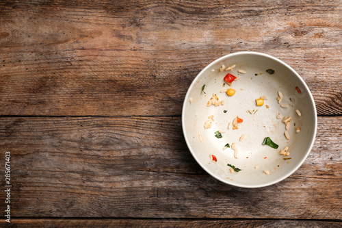 Dirty bowl with food leftovers on wooden background, top view Wallpaper Mural
