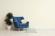 Leinwanddruck Bild - Stylish room interior with comfortable armchair and plant near beige wall. Space for text