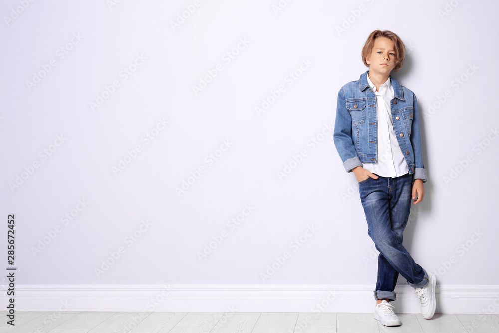 Fototapety, obrazy: Cute little boy in casual outfit near white wall. Space for text