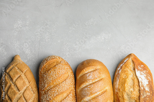 Foto op Plexiglas Bakkerij Loaves of different breads on grey background, flat lay. Space for text