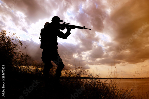 Poster Chasse Soldier with machine gun patrolling outdoors. Military service