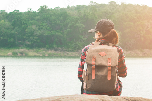 Hipster young girl with bright backpack enjoying sunset on peak mountain. Travel Lifestyle adventure concept vacations into the wild.