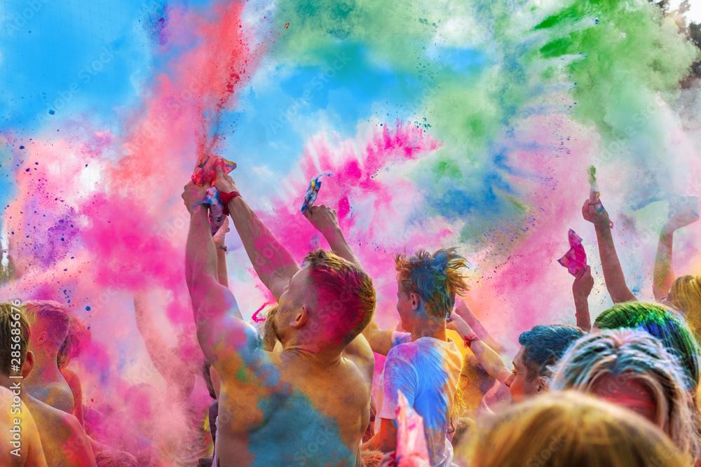 Fototapeta Holi Fest begeisterte Menschen jubeln auf einem Holifestival, tanzen und werfen mit buntem Holipulver
