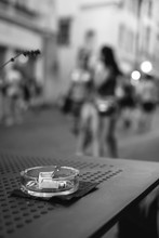 Black And White, An Ashtray With Cigarette Butts On A Restaurant Table On An Evening City Street, A Vase And A Menu, People In The Background. Smoking Concept, Harmful To Health, Vertical Photo