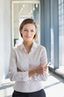 Confident young businesswoman standing while holding smartphone in office