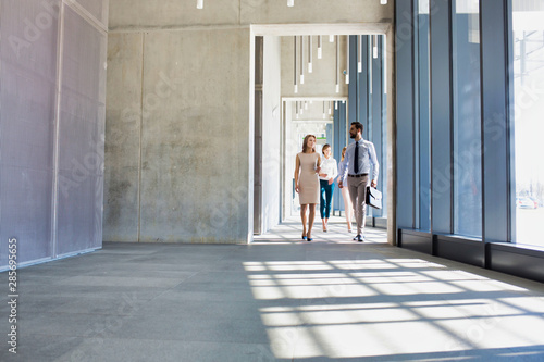 Fototapeta Business people walking in office corridor