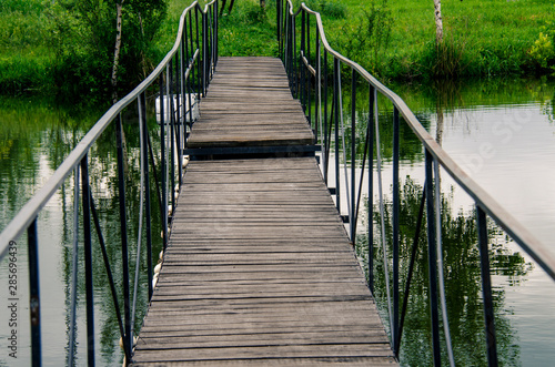 Fototapeten Forest river A narrow wooden bridge with metal railings leads across the river to the shore