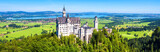 Neuschwanstein castle in Munich vicinity, Bavaria, Germany. This fairytale castle is a famous landmark of Germany. Landscape with mountains and Neuschwanstein castle. Scenic panoramic view in summer.