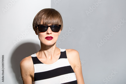 Beautiful woman with brown short hair wearing stripes dress over white and grey background Fotobehang