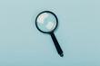 Leinwanddruck Bild - Small magnifying glass on pastel blue background