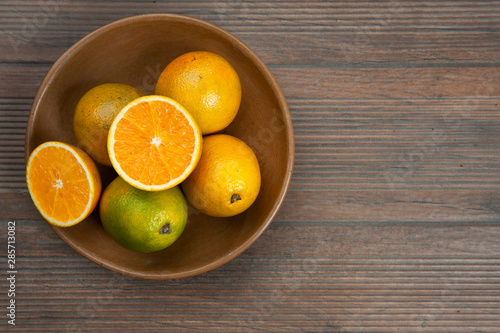 Oranges, vitamin C, in a clay bowl, brown.A half cut orange.Autumn wood color background.View from above.Space for text.