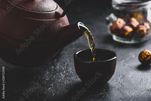 Spoed Fotobehang Thee Pouring ready red tea into tea bowl