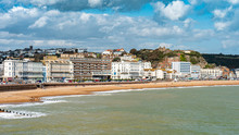 Hastings Castle And Seafront, England. The Seafront To The East Sussex Town Of Hastings With Its Landmark Castle Visible On Top Of The Hill.