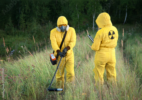 Two dosimetrist  in protective suite and mask with geiger counter measuring radi Canvas Print