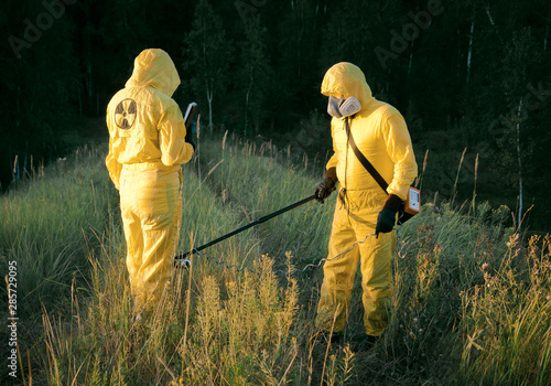 Photo  Two dosimetrist  in protective suite and mask with geiger counter measuring radi