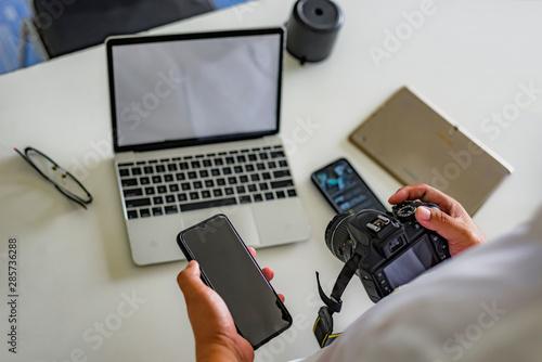 Fototapeta Male hand hold photo camera office. Computer technology background. Studio shot. Creative image. obraz na płótnie