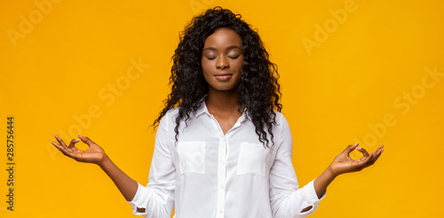 Cuadros en Lienzo  Peaceful afro girl with closed eyes practicing breathing yoga