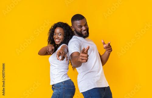 Obraz na plátně Joyful young black couple pointing fingers at camera